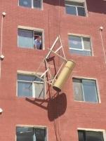 """大奖娱乐pt_太阳能热水器被风吹落 悬在头顶的""""高空杀手"""""""